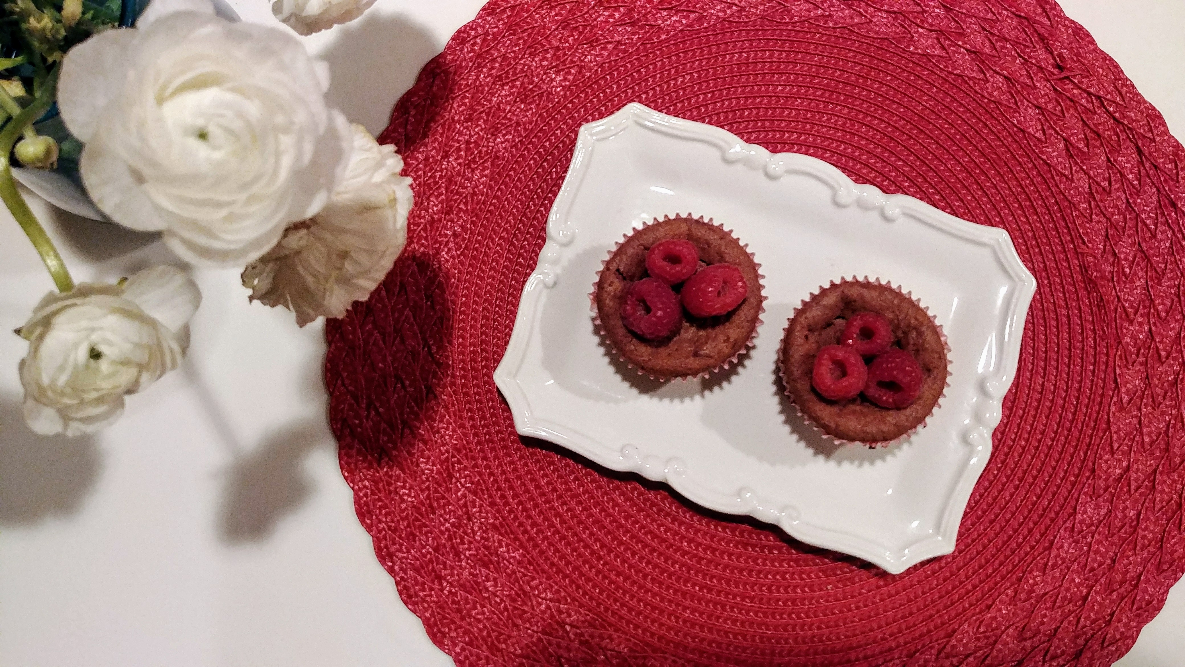 Raspberry Cupcakes topped with fresh raspberries next to white flowers on table